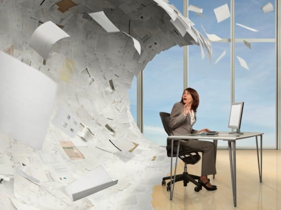 Wave of Paperwork About to Crash On a Businesswoman - Photo courtesy of ©iStockphoto.com/Blend_Images, Image #15931063