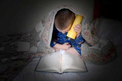 A little boy reading a good book by flashlight