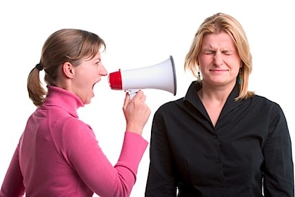 one woman yelling at another woman with a mergaphone