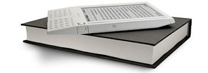 the amazon kindle sitting on top of a traditional book