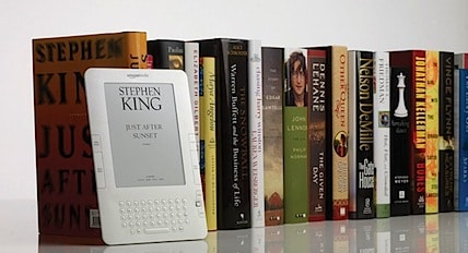 a kindle 2 sitting up against a shelf of traditional books
