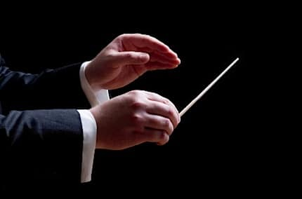 a conductors hands in the middle of a concert