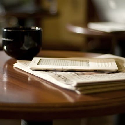 the kindle 2 sitting on top of a traditional newspaper