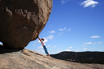 a girl keeping a huge rock from rolling down on top of her