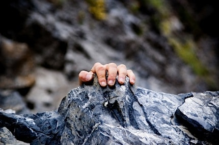 a man getting his hand on the rock above to scale the mountain