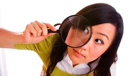 a girl looking through a magnifying glass so that one eye is really magnified