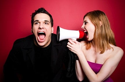 a woman shouting at a man through a bull horn