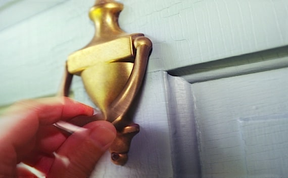 A Man's Hand on Brass Door Knocker - Photo courtesy of ©iStockphoto.com/KenTannenbaum, Image #6975278