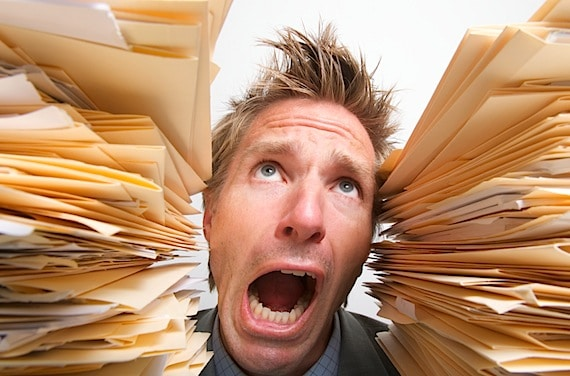 Worker gets the squeeze from some stacks of file folders - Photo courtesy of ©iStockphoto.com/PeskyMonkey, Image #8186932