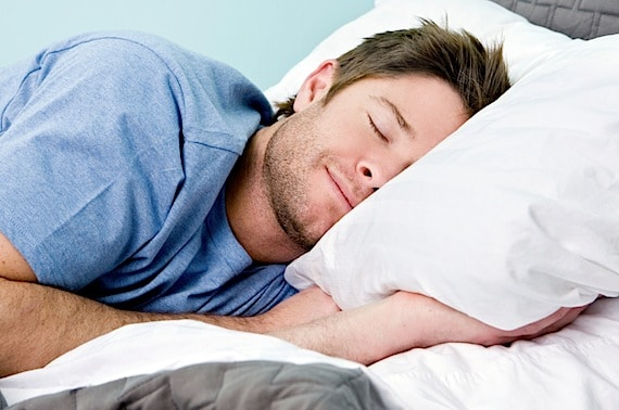 Man comfortably sleeping in his bed - Photo courtesy of ©iStockphoto.com/sswartz, Image #9674561