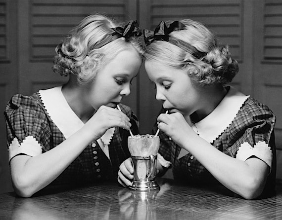 Two Twin Sisters Drinking from the Same Glass with Different Straws - Photo courtesy of ©iStockphoto.com/HultonArchive, Image #13312193