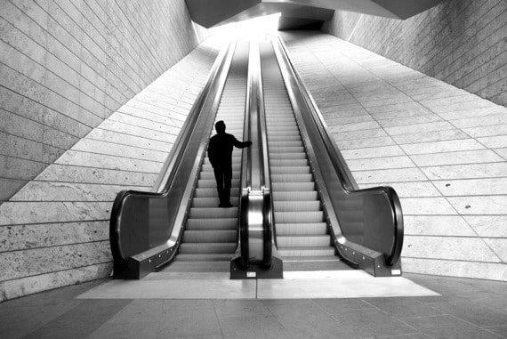 Man Riding an Escalator to the Next Level - Photo courtesy of ©iStockphoto.com/ilbusca, Image #9889860