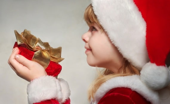 Girl Giving Gift at Christmas - Photo courtesy of ©iStockphoto.com/nautilus_shell_studios, Image #10149473