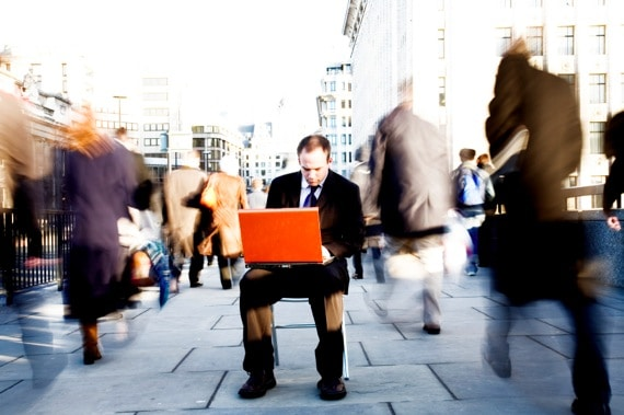 A Businessman Working in the Midst of a Crowd - Photo courtesy of ©iStockphoto.com/urbancow, Image #4776338