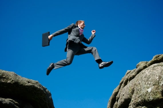 Man Leaping Courageously Over a Gap Between Two Rocks - Photo courtesy of ©iStockphoto.com/PeskyMonkey, Image #10996669