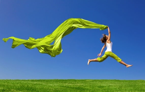 Woman Jumping on a Green Meadow with a Green Cloth - Photo courtesy of ©iStockphoto.com/erikreis, Image #12345727
