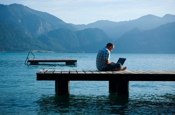 Man Sitting on a Dock with a Laptop - Photo courtesy of ©iStockphoto.com/Claudiad, Image #10484365