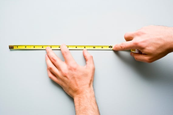 Men's Hands Holding a Measuring Tape Against a Wall - Photo courtesy of ©iStockphoto.com/michellegibson, Image #14720530