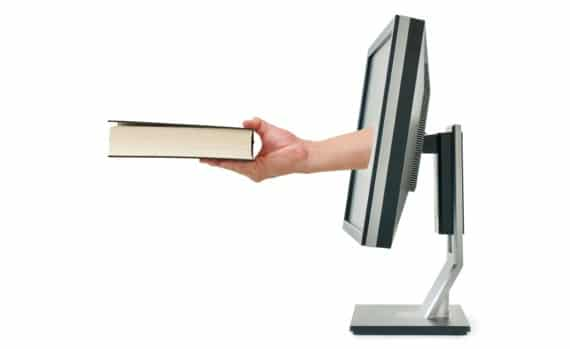 A Hand Coming Out of a Computer Monitor with a Book - Photo courtesy of ©iStockphoto.com/BsWei, Image #12942957