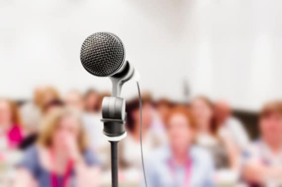 A Microphone Stand in Front of an Out of Focus Audience - Photo courtesy of ©iStockphoto.com/RapidEye, Image #15805678