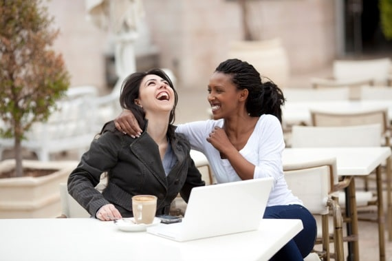 Two friends laughing in an outdoor café - Photo courtesy of ©iStockphoto.com/RuslanDashinsky, Image #15345841