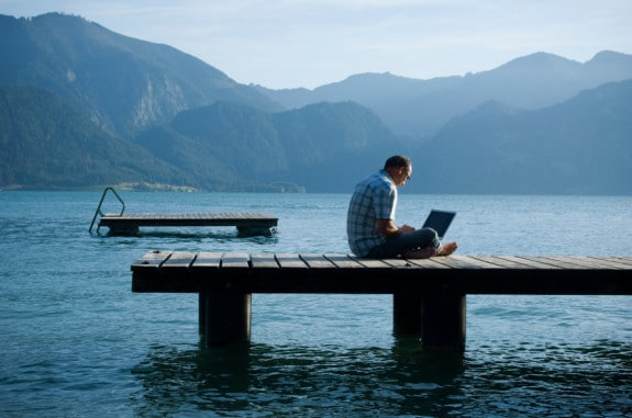Man Sitting on a Dock with His Computer - Photo courtesy of ©iStockphoto.com/Claudiad, Image #10484365