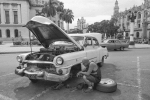 Broken Down Car with Owner Trying to Change the Tire