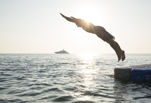 Man dives into tranquil sea, from pier, boat