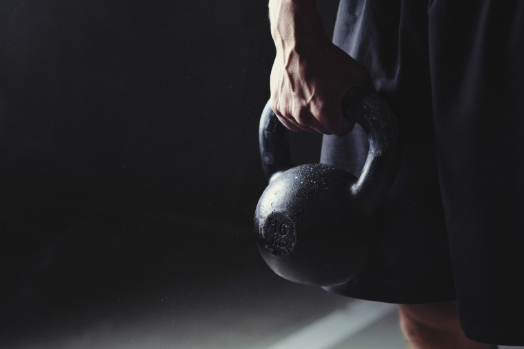 Close-up of a muscular hand holding a kettlebell