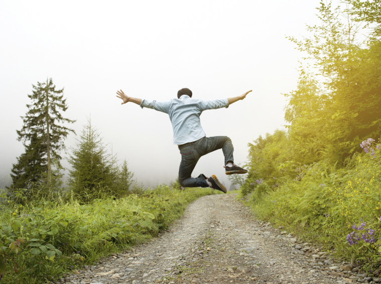 Man jumping on a country road, rear view
