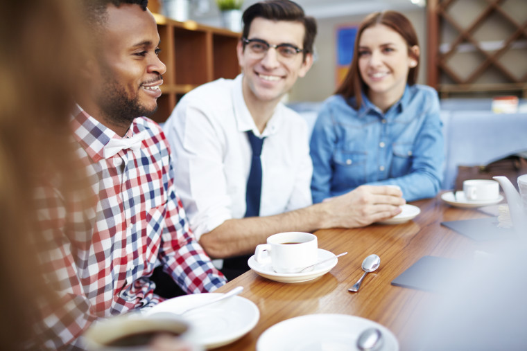 Multi-ethnic group of young people talking over a cup of coffee