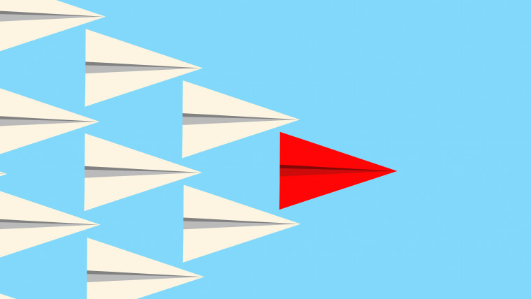 Leadership concept illuctration showing a red paper plane leading a group of white planes. Vector format available.