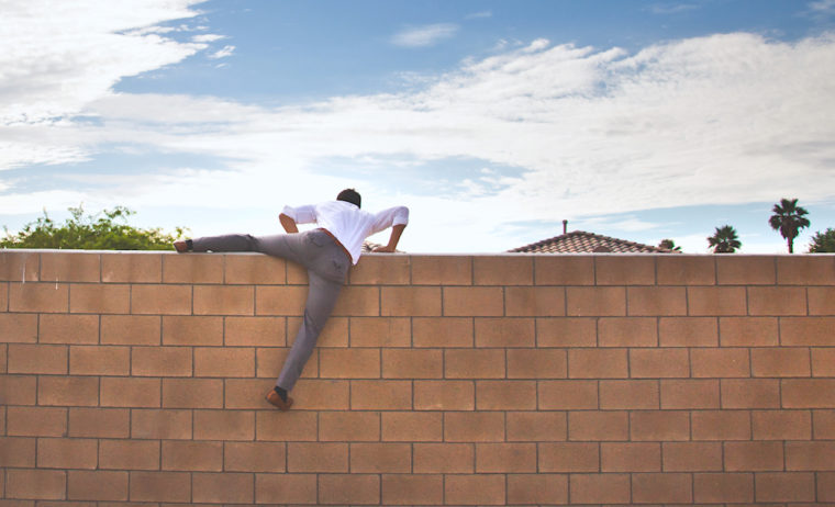 man climbing over a brick wall