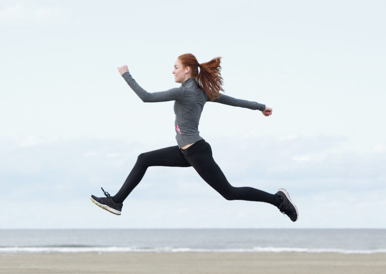 Young woman running and jumping