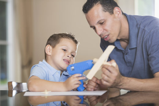 father and son building wooden airplane model